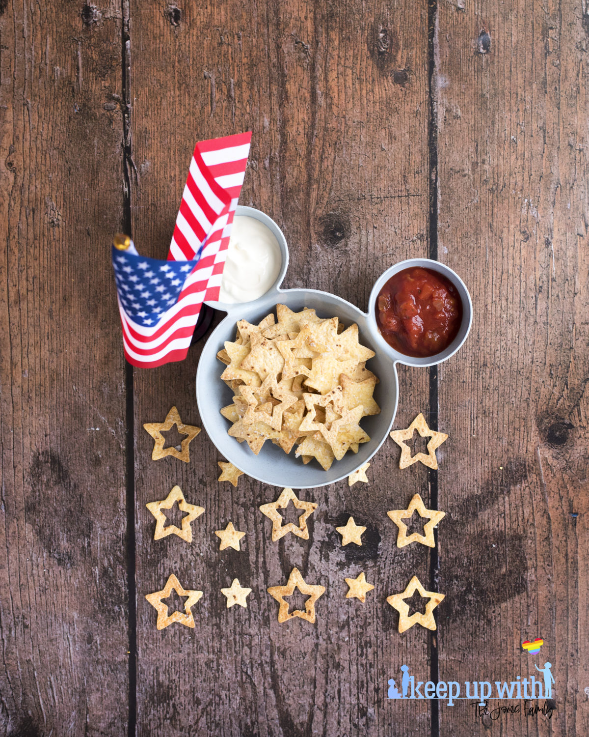 Image shows a blue bowl in the shape of Mickey Mouse suitable for chips 'n' dip. There is an American flag stood close to the bowl and inside the bowl is tomato salsa, soured cream, and star spangled nacho chips. Image by keep up with the jones family.