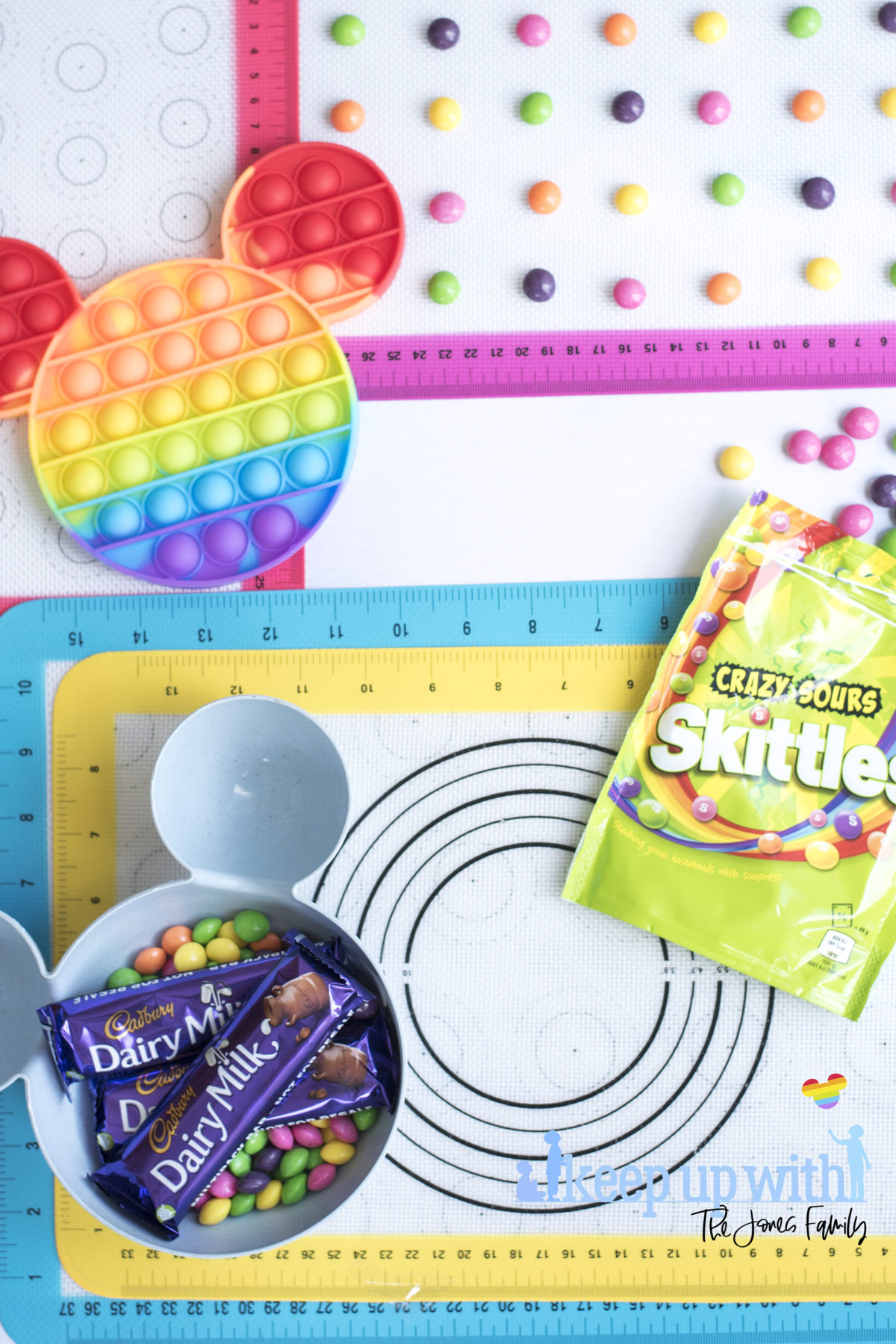 Image shows a rainbow coloured pop-it toy on top of rainbow coloured silicone baking trays. There is a blue mickey mouse shaped bowl full with skittles sweets and the packet by the side.  A Disney's Mickey Mouse Pop-It Chocolate Bar. Image by Keep Up With the Jones Family.