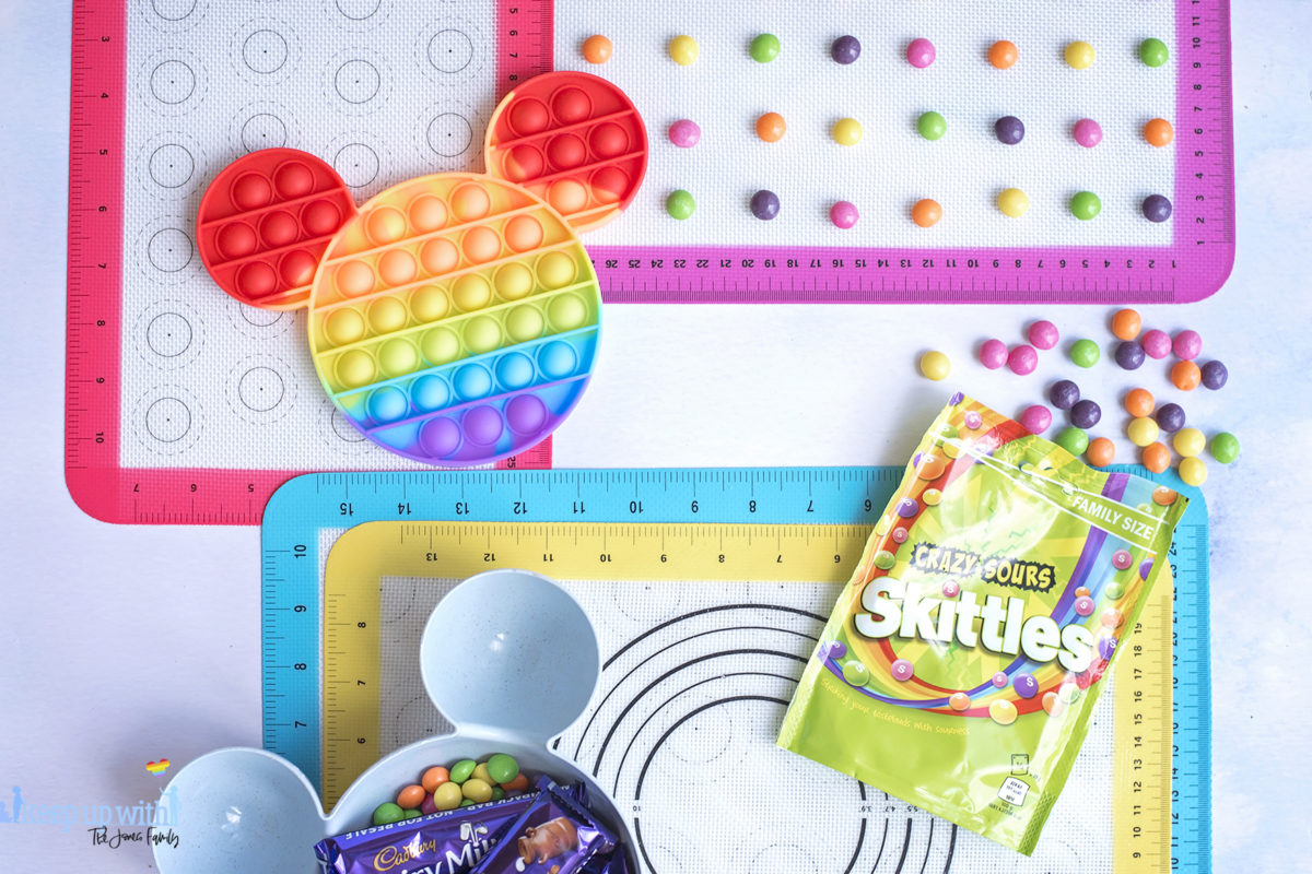 Image shows the ingredients for a Disney's Mickey Mouse Pop-It Chocolate Bar. IA rainbow coloured pop-it toy in the shape of Mickey Mouse, and some skittles sweets and candy.  Image by Keep Up With the Jones Family.