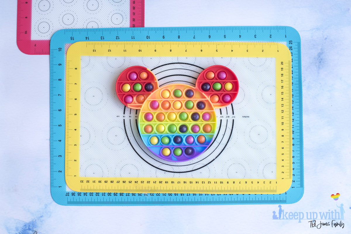 Image shows a Mickey Mouse shaped rainbow coloured silicone pop-it toy filled with skittles ready to make a Mickey Mouse Chocolate Pop-It bar. Image by Keep Up With the Jones Family.