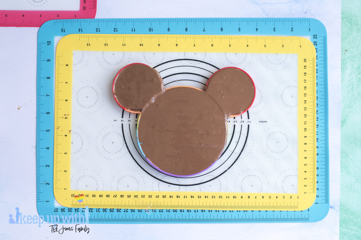 Image shows a rainbow coloured mickey mouse shaped pop-it toy filled with melted chocolate, ready to make a mickey mouse chocolate pop-it bar. Image by keep up with the jones family.