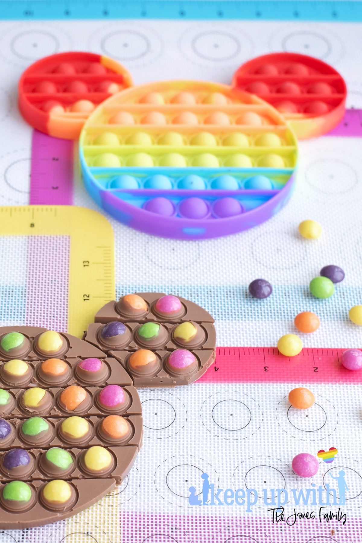 Image shows a rainbow Pop-It toy in the shape of Mickey Mouse on rainbow silicone baking trays, surrounded by skittles sweets and a chocolate bar dotted with the sweets. A Disney's Mickey Mouse Pop-It Chocolate Bar. Image by Keep Up With the Jones Family.