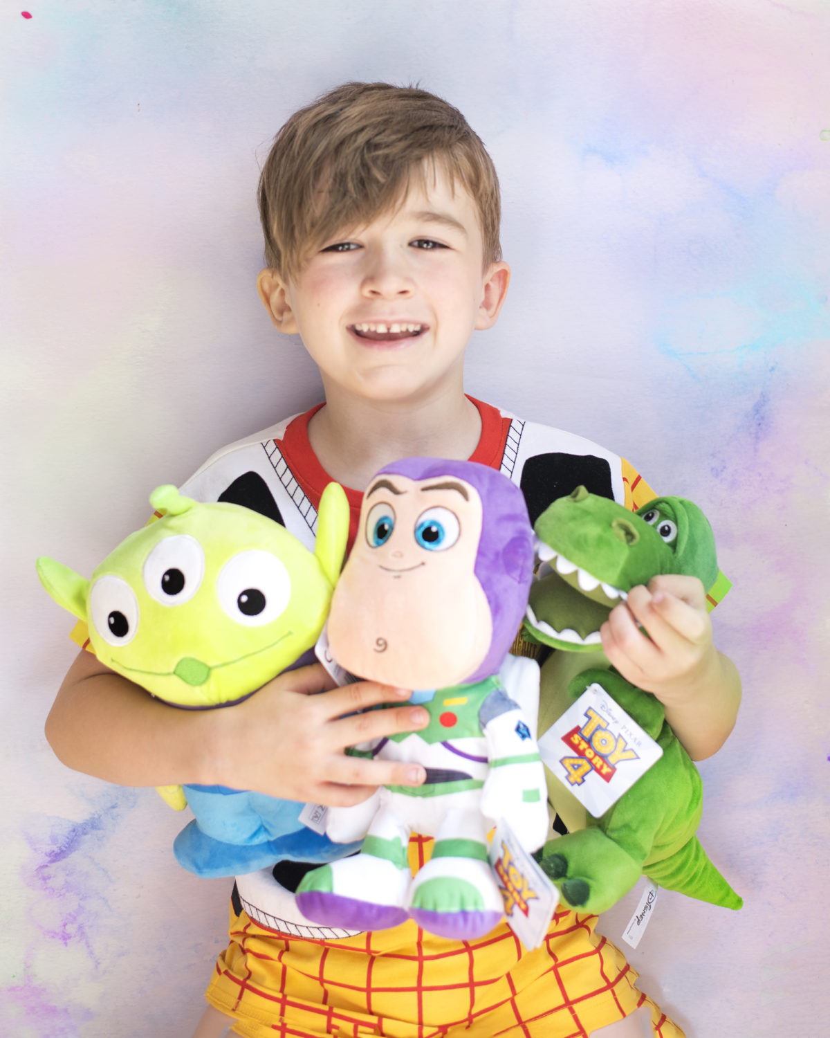 Image shows a young boy dressed in a Disney's Toy Story Woody t-shirt from NEXT, colding three Disney Pixar's Toy Story characters in his arms - Dinosaur, Rex, Buzz Lightyear and an Alien as plush toys from SImba Toys. Image by Keep Up With The Jones Family.