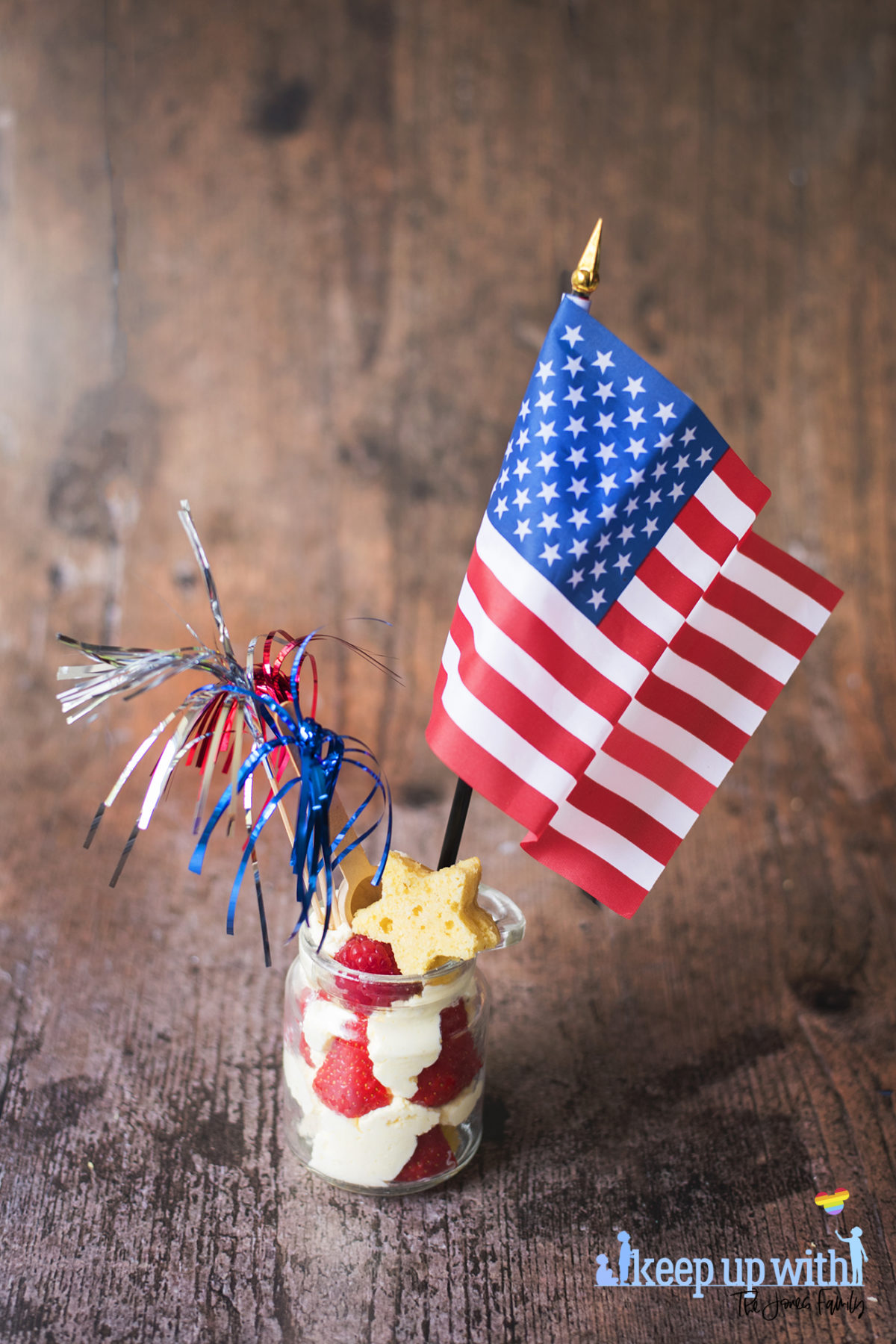 Image shows a 4th July Strawberry Cake Jar dessert on a dark wooden tabletop. The jar contains piped whipped cream and strawberries, with stars cut out of vanilla angel cake inside and on top. There is an american flag and three metallic firework sparklers in red, white and blue sticking out of the jar. Image by Sara-Jayne Jones of Keep Up With The Jones Family.