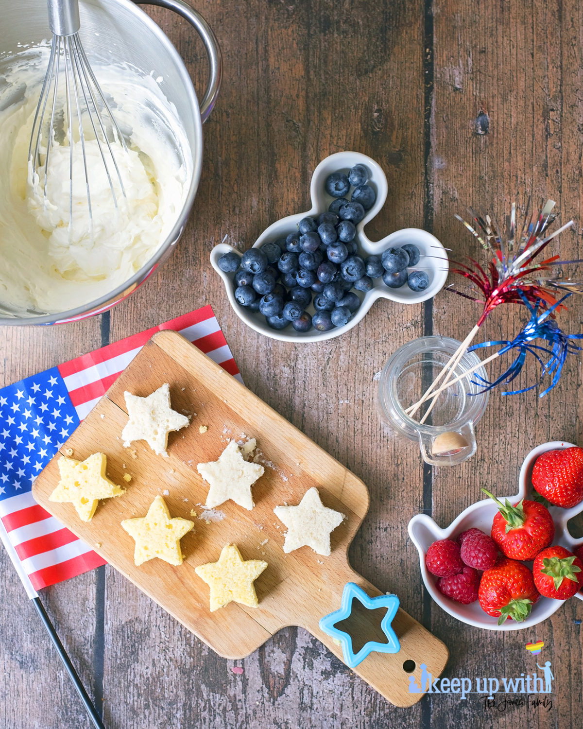 Image shows the ingredients needed to make 4th July Strawberry Cake Jar desserts, on top of a dark wooden tabletop. Strawberries, whipped cream, angel cake, and blueberries. Image by Sara-Jayne Jones of Keep Up With The Jones Family.
