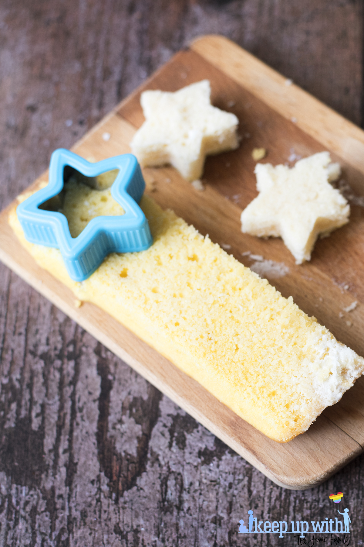 Image shows vanilla angel cake stars being cut from a slice of cake using a blue star cookie cutter, on top of a wooden chopping board, resting on a dark wooden tabletop. Image by Sara-Jayne Jones of Keep Up With The Jones Family.