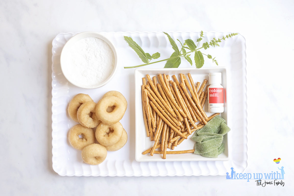 Image shows ingredients for Back to School Doughnuts on a white scalloped tray, sitting on a white marble surface. There are mini doughnuts, pretzel sticks, green fizzy belt sweets, mint leaves, red oil based food colouring and a bowl of icing sugar. Image by Sara-Jayne from Keep Up With The Jones Family.