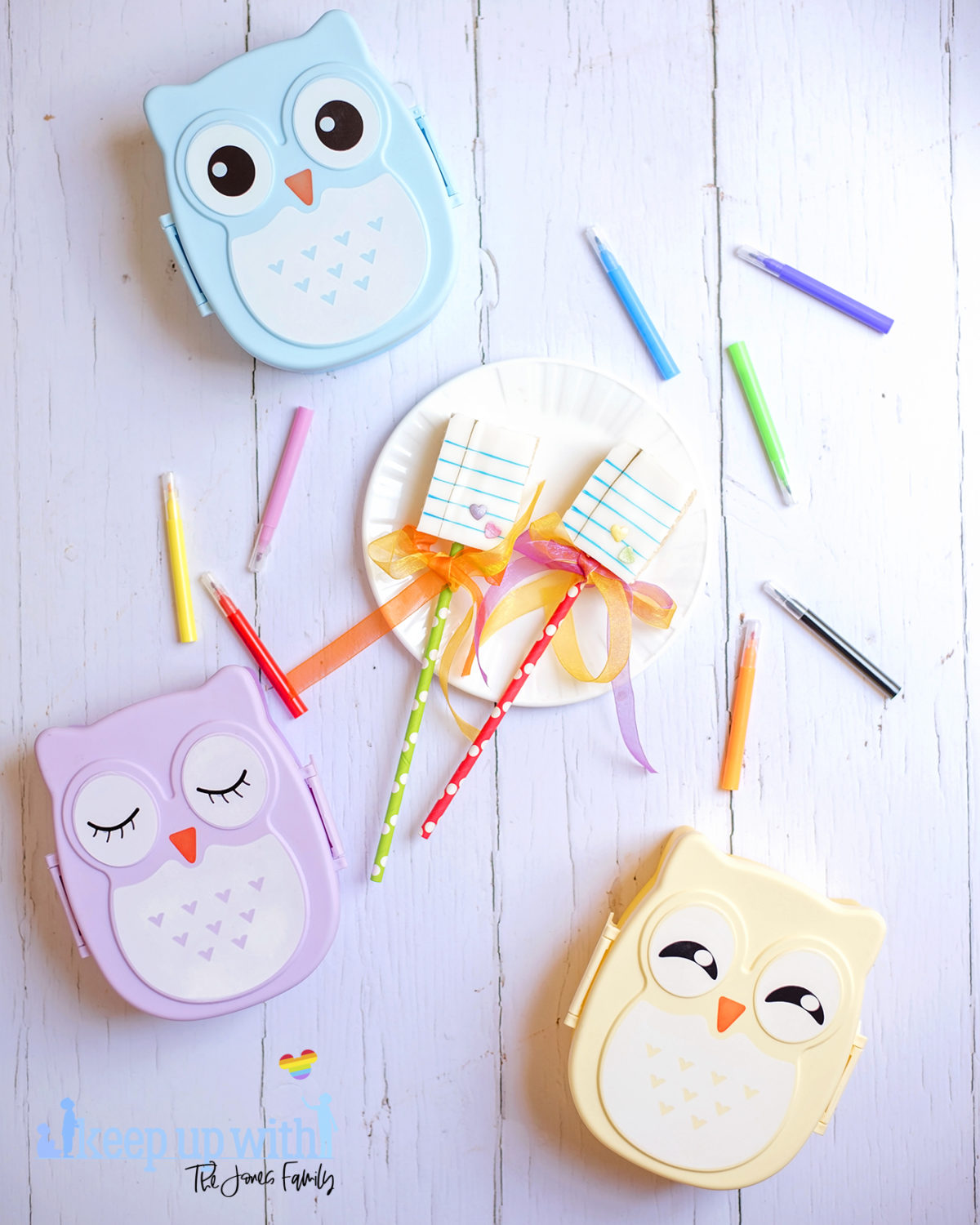 Image shows Back to School Rice Krispie Lollipop treats on a white Vera Wang for Wedgwood plate. There are three pastel coloured owl bento boxes in the background and a small tin bucket of Crayola crayons alongside it. Cake pens surround the plate on the white wooden background. Image by Sara-Jayne from Keep Up With The Jones Family.