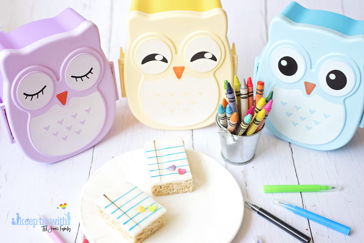Image shows Back to School Rice Krispie treats on a white Vera Wang for Wedgwood plate. There are three pastel coloured owl bento boxes in the background and a small tin bucket of Crayola crayons alongside it. Cake pens surround the plate on the white wooden background. Image by Sara-Jayne from Keep Up With The Jones Family.