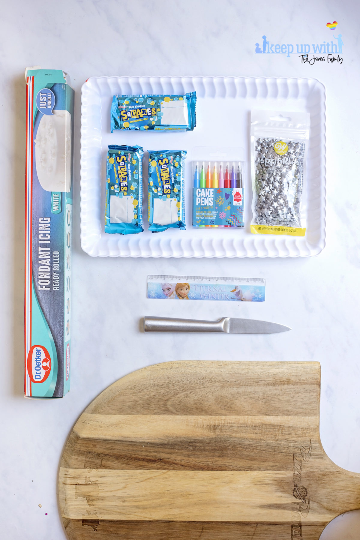 Image shows ingredients for Back to School Rice Krispie treats on a white scalloped tray, sitting on a white marble surface. There are Rice Krispies Squares Bars, sprinkles, white pre-rolled royal icing fondant, cake pens, a ruler, knife and shopping board. Image by Sara-Jayne from Keep Up With The Jones Family.