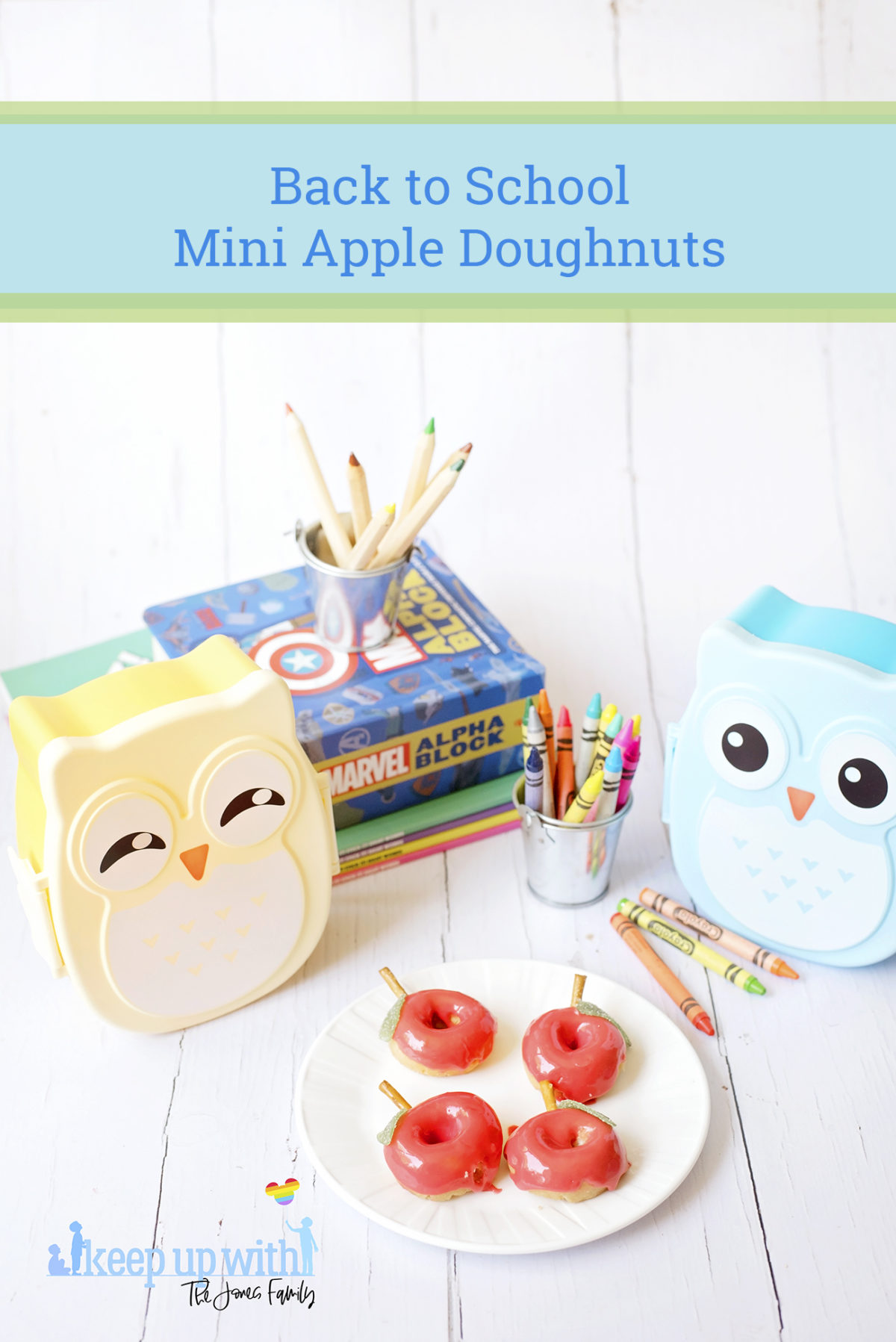 Image shows red apple shaped Back to School Doughnuts on a white Vera Wang plate, sitting on a white wooden surface. There are two small owl shaped bento boxes and books in the background, along with a bucket of crayola crayons. Image by Sara-Jayne from Keep Up With The Jones Family.