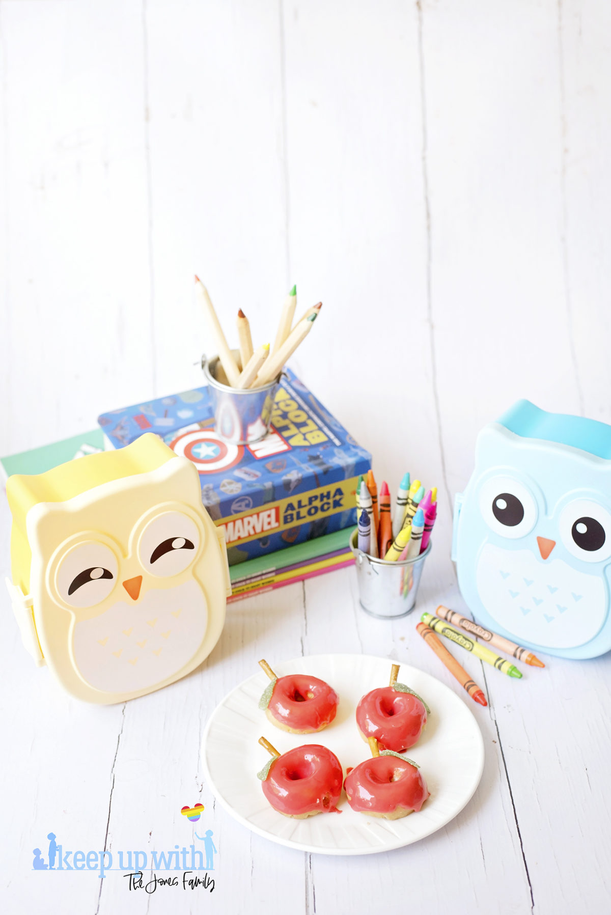 Image shows Back to School Doughnuts on a white Vera Wang plate, sitting on a white wooden surface. There are small owl shaped bento boxes and books in the background, along with a bucket of crayola crayons. Image by Sara-Jayne from Keep Up With The Jones Family.