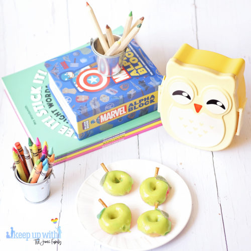 Image shows green apple shaped Back to School Doughnuts on a white Vera Wang plate, sitting on a white wooden surface. There are two small owl shaped bento boxes and books in the background, along with a bucket of crayola crayons. Image by Sara-Jayne from Keep Up With The Jones Family.