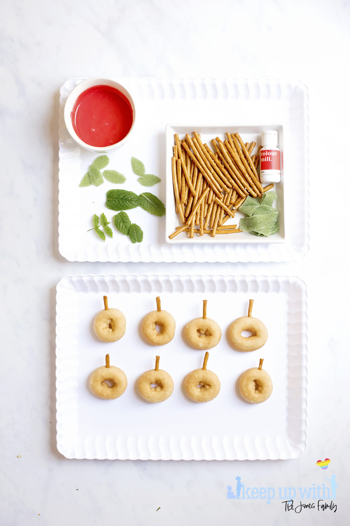 Image shows ingredients for Back to School Doughnuts on a white scalloped tray, sitting on a white marble surface. There are mini doughnuts, pretzel sticks, green fizzy belt sweets, mint leaves, red oil based food colouring and a bowl of icing sugar coloured red. Beneath the tray is a second tray with the mini donuts prepared with pretzel stalks in. Image by Sara-Jayne from Keep Up With The Jones Family.