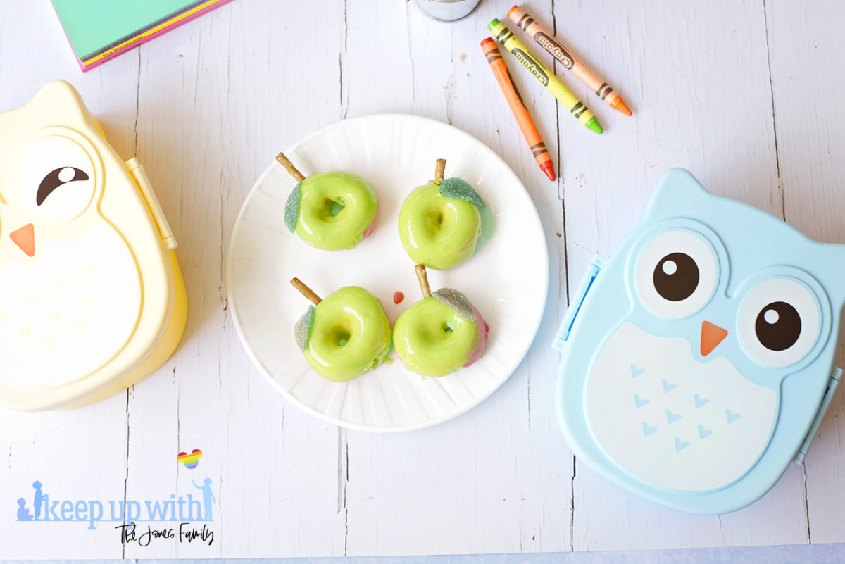 Image shows a flatlay of green apple shaped Back to School Doughnuts on a white Vera Wang plate, sitting on a white marble surface. Two owl shaped bento boxes and crayola crayons are in the photograph. Image by Sara-Jayne from Keep Up With The Jones Family.