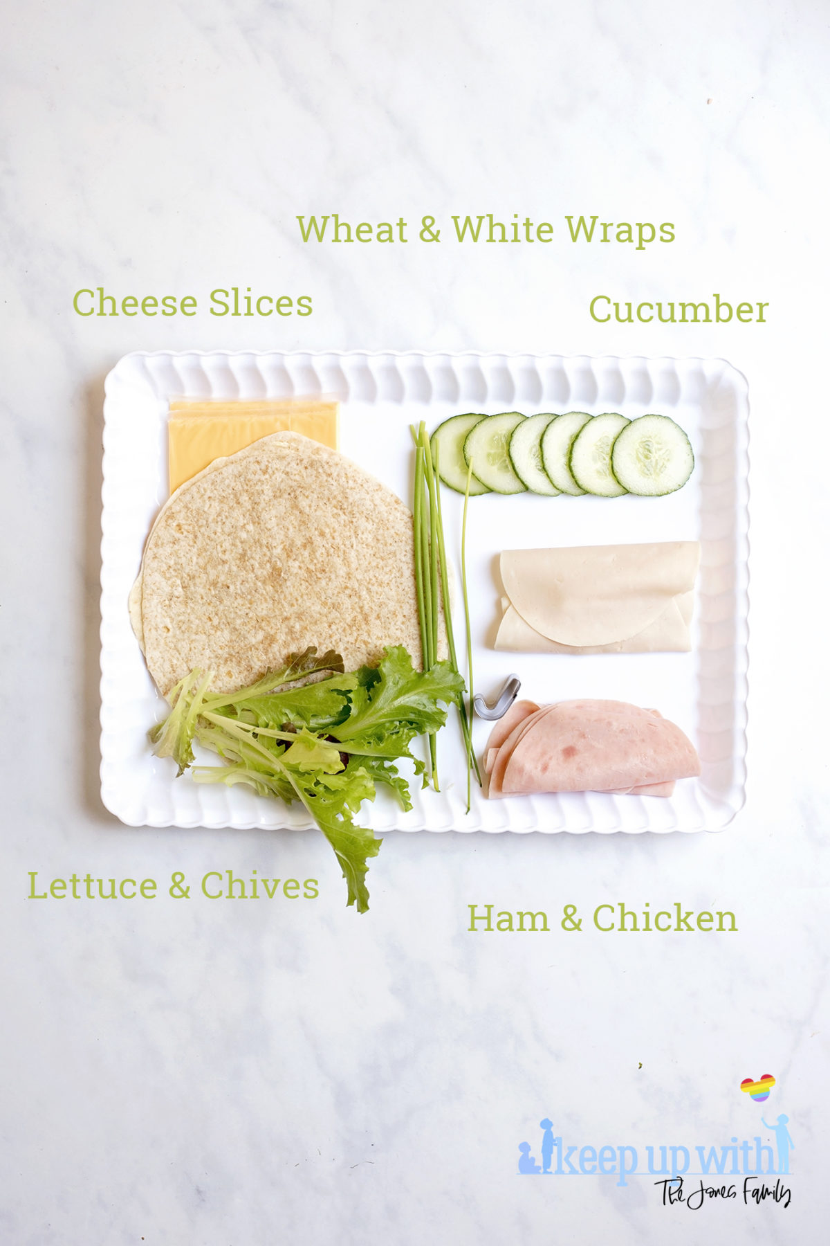 Image shows ingredients needed to make Book Sandwich Wraps. On a white scalloped tray, sat on a white marble top, are two white and wheat wraps, cucumber, ham and chicken slices, lettuce leaves, chives and cheese slices. Image by Sara-Jayne of Keep Up With The Jones Family.