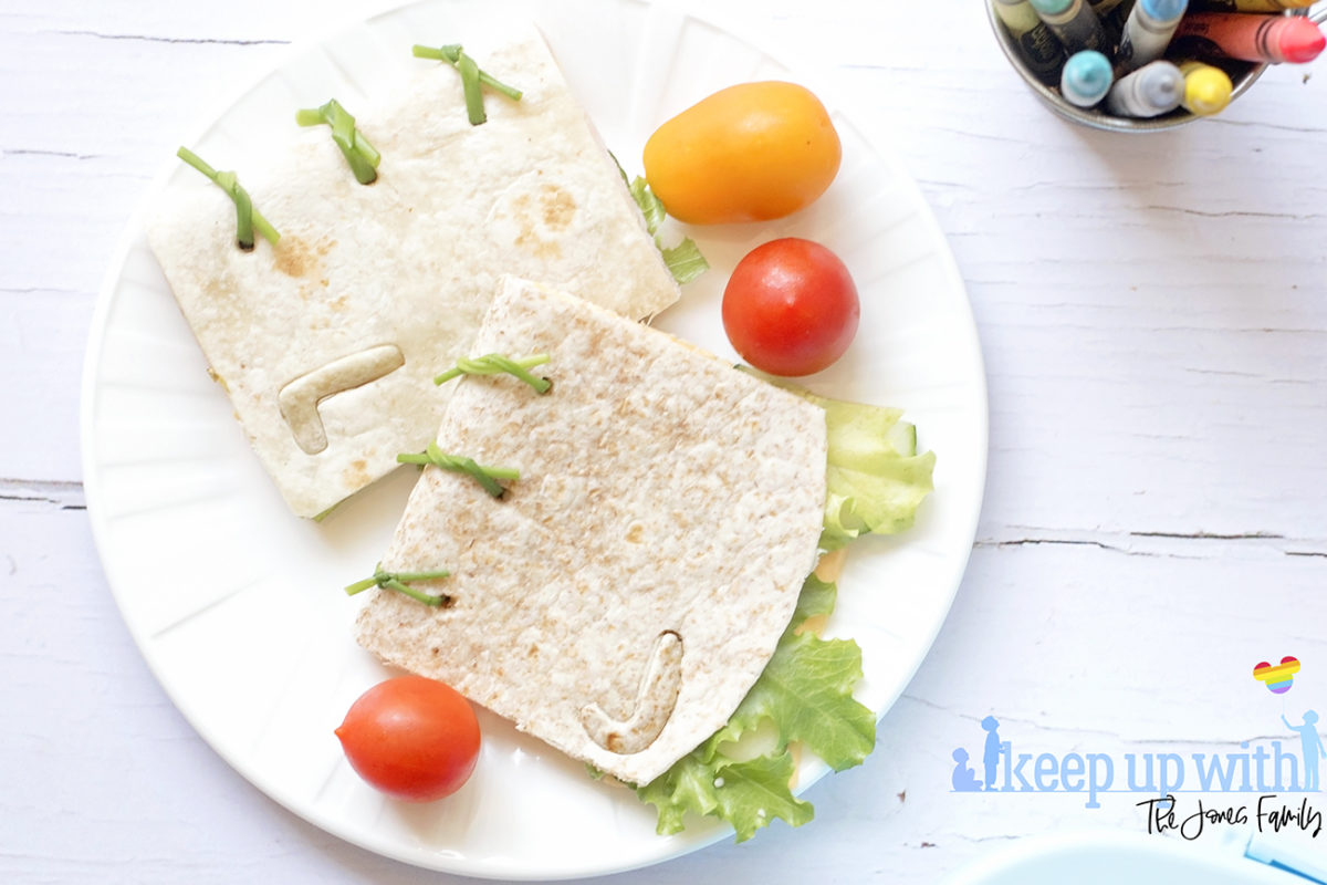 Image shows Book sandwich wrap fun food on a white vera wang plate, surrounded by orange and red cherry tomatoes. Image by Sara-Jayne from Keep Up With The Jones Family.