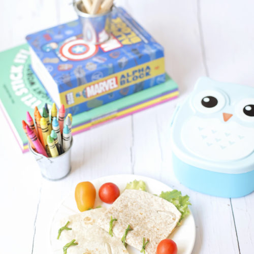 Image shows Book Sandwich Wraps on a white Vera Wang plate, resting on a white wooden surface surrounded by a blue owl lunchbox, a tin bucket of crayola crayons in various colours and a stack of books including Mrs Wordsmith and Marvel Alphablock. Image by Sara-Jayne of Keep Up With the Jones Family.