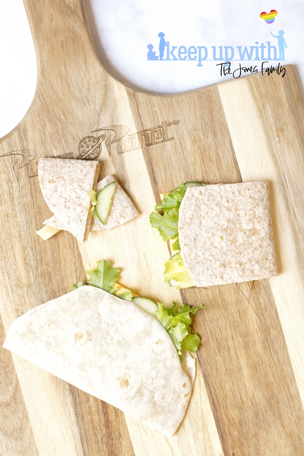 Image shows step two of how to make a book sandwich wrap. On a toy story wooden chopping board sits two wraps filled with ingredients, folder over and one of them is chopped into a booklet shape. Image by Sara-Jayne from Keep Up With The Jones Family.