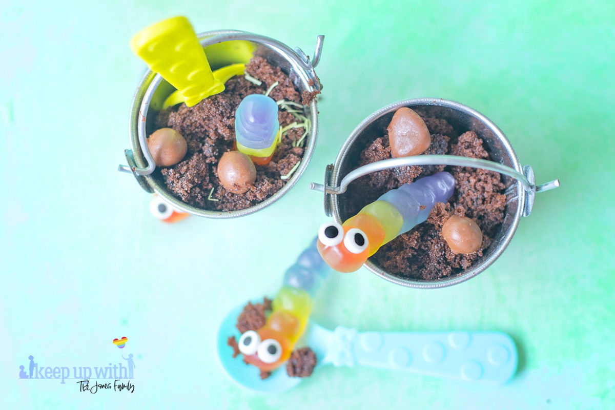 Image shows Buckets of Dirt 'n' Worms Dessert - two little galvanised steel buckets containing chocolate cake made to look like mud and gummy worms with little eyes in them. There are coloured plastic spoons for eating the desserts. Image by Sara-Jayne of Keep Up With The Jones Family.