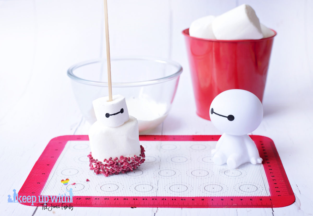 Image shows a plastic Baymax figure from Disney Pixar's Big Hero 6 sat on a white tabletop. In front of him is a fruity baymax marshmallow pop sat on a silicone baking mat. In the background is a glass bowl containing melted white candy drops and a red tin bucket of large marshmallows. Image by Keep Up With The Jones Family.