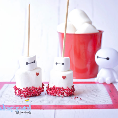 Image shows a plastic Baymax figure from Disney Pixar's Big Hero 6 sat on a white tabletop. In front of him are two fruity baymas marshmallow pops sat on a silicone baking mat. In the background is a red tin bucket of large marshmallows. Image by Keep Up With The Jones Family.