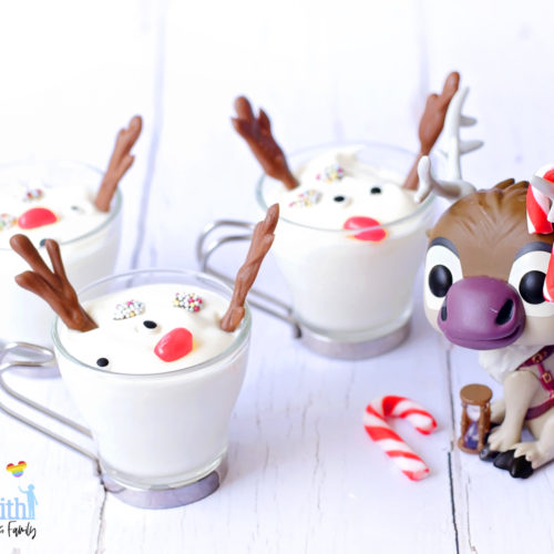 Image shows a Disney's Frozen Sven the Reindeer Funko Pop Vinyl decorated with mini red and white peppermint candy canes on his antlers. The figure is sitting next to three Melted Sven the Reindeer Yoghurts in glass cups with silver handles, on a white wooden tabletop. Image by Keep Up With The Jones Family.