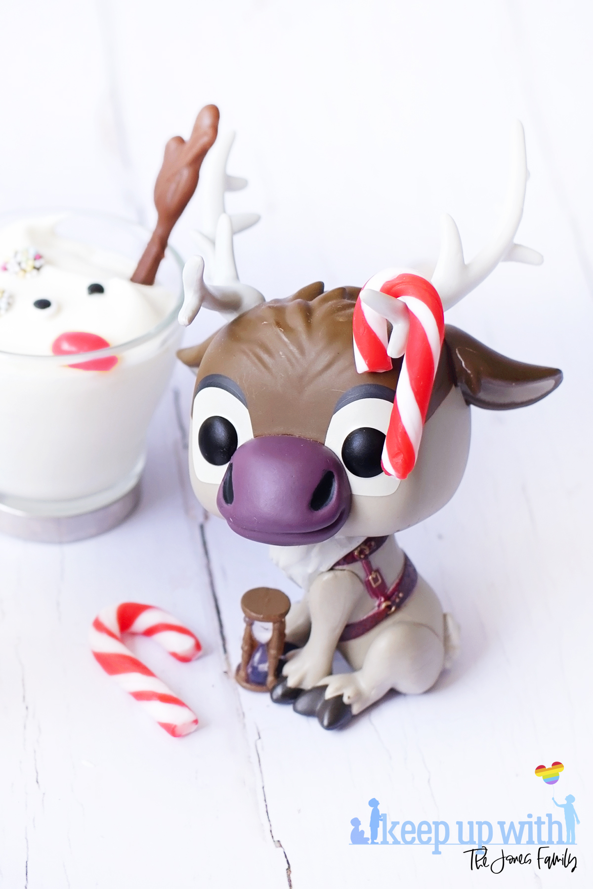 Image shows a Disney's Frozen Sven the Reindeer Funko Pop Vinyl decorated with mini red and white peppermint candy canes on his antlers. The figure is sitting next to a Melted Sven the Reindeer Yoghurts in glass cups with silver handles, on a white wooden tabletop. Image by Keep Up With The Jones Family.