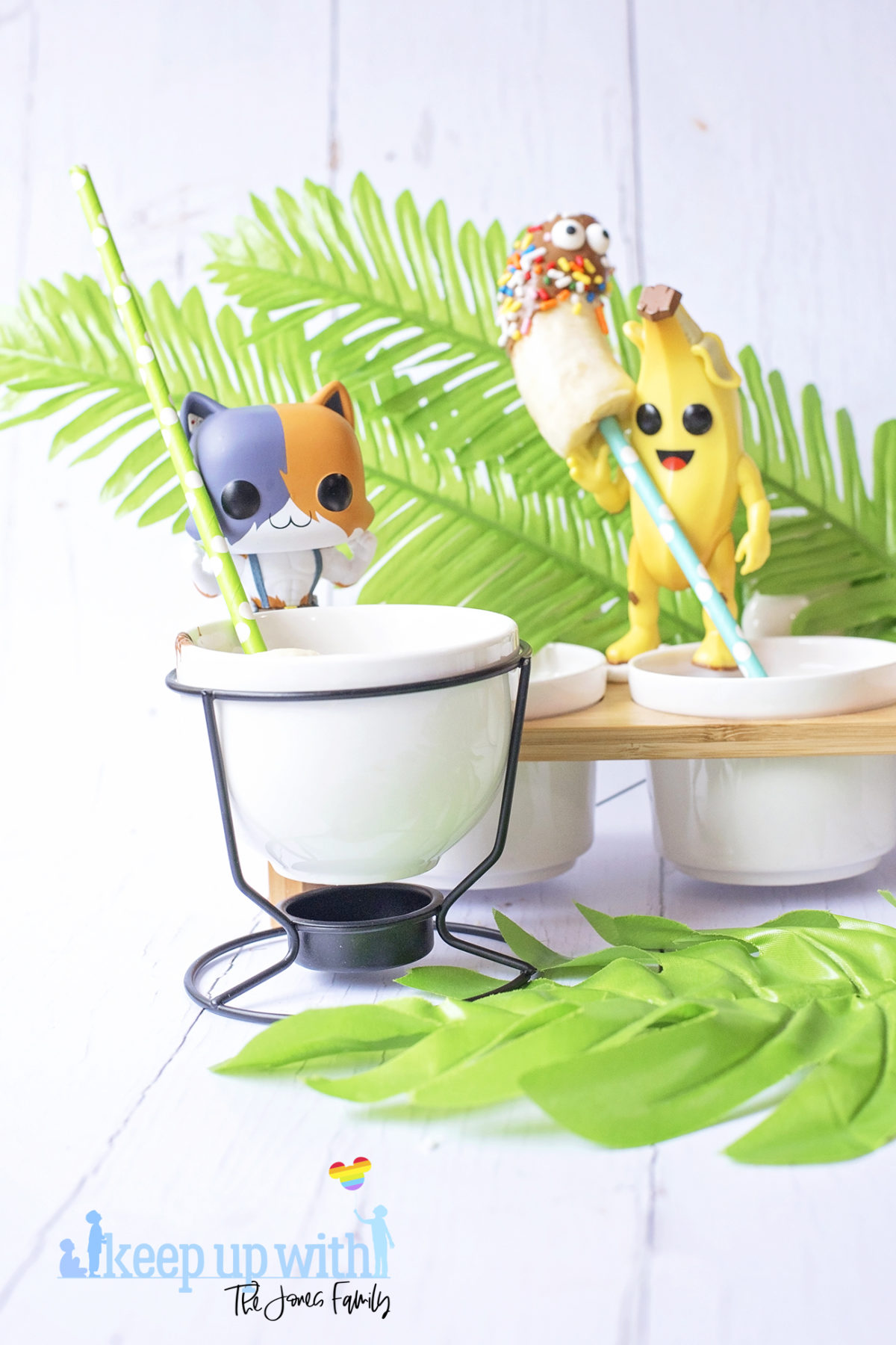 Image shows Peely's Banana Fortnite Fondue Bar, fun food for families. A Funko Pop Vinyl Peely and Meowscles stand on a fondue bar stirring chocolate with bananas on sticks. Image by Sara-Jayne from Keep Up With The Jones Family.