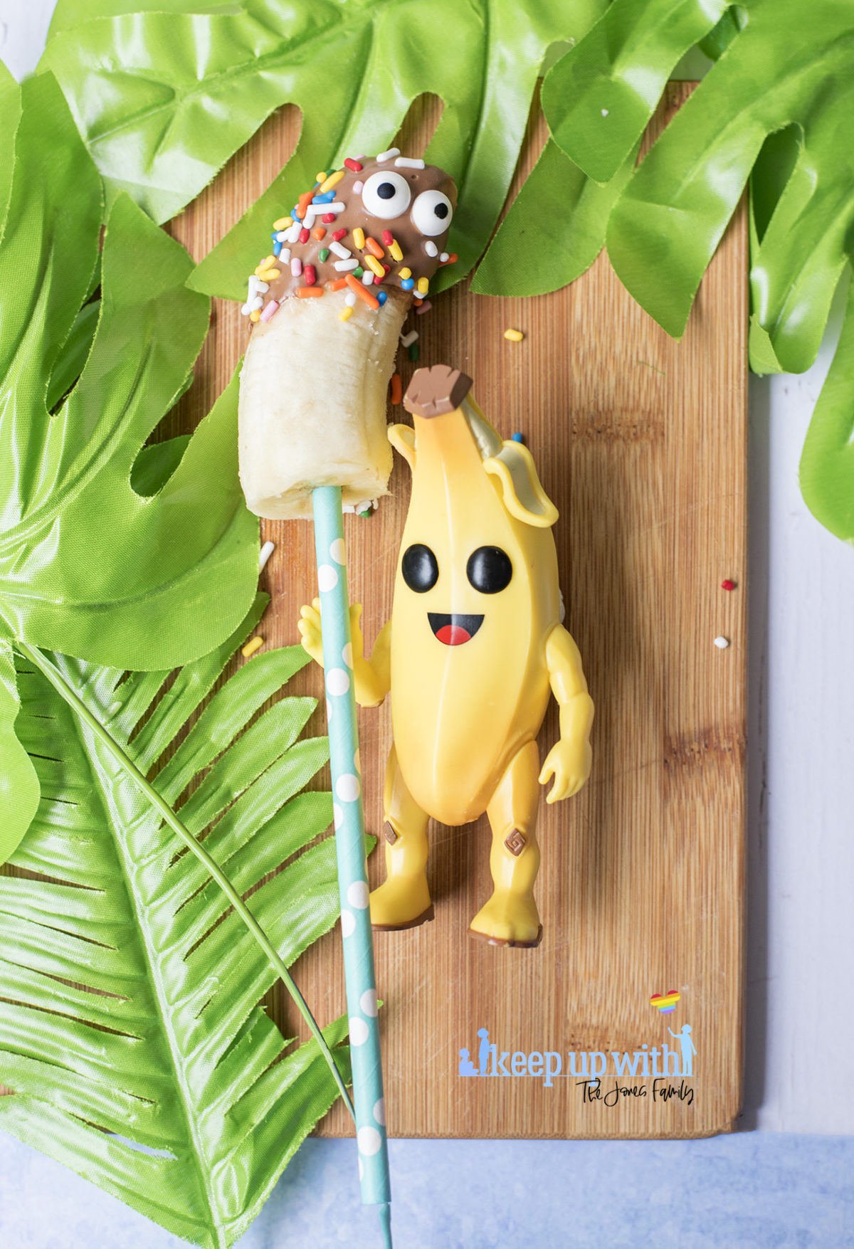 Image shows Peely's Banana Fortnite Fondue Bar, fun food for families. A Funko Pop Vinyl Peely lies on a wooden board, holding a bands covered in chocolate, sprinkles and edible eyes. Image by Sara-Jayne from Keep Up With The Jones Family.