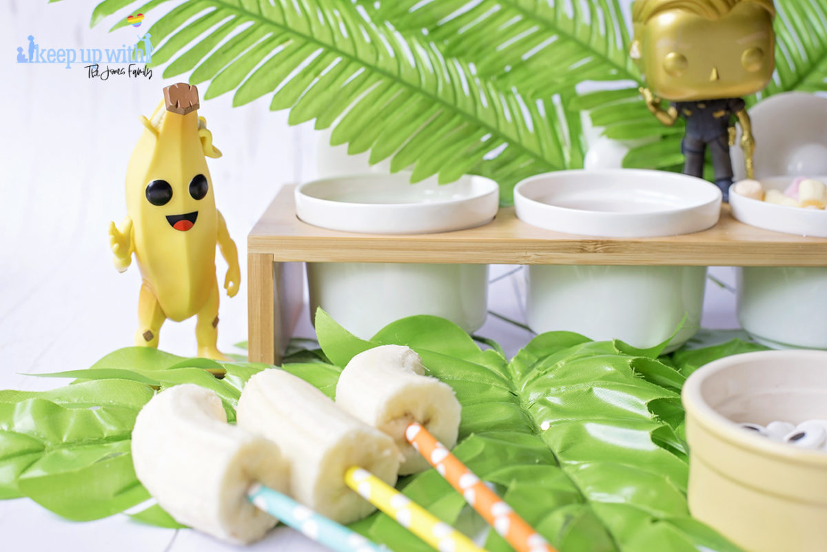 Image shows Peely's Banana Fortnite Fondue Bar, fun food for families. A Funko Pop Vinyl Peely stands on a fondue bar next to bananas on spotted coloured straws. Image by Sara-Jayne from Keep Up With The Jones Family.