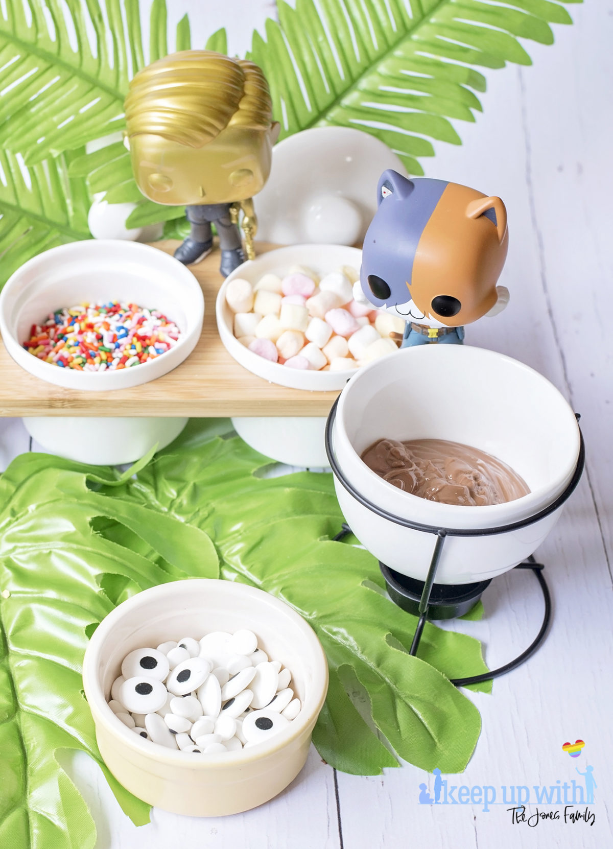 Image shows Peely's Banana Fortnite Fondue Bar, fun food for families. A Funko Pop Vinyl Meowscles and Midas stand on a fondue bar next to dishes of fondue toppings including edible eyes, sprinkles, mini marshmallows and peanut butter drops. Image by Sara-Jayne from Keep Up With The Jones Family.
