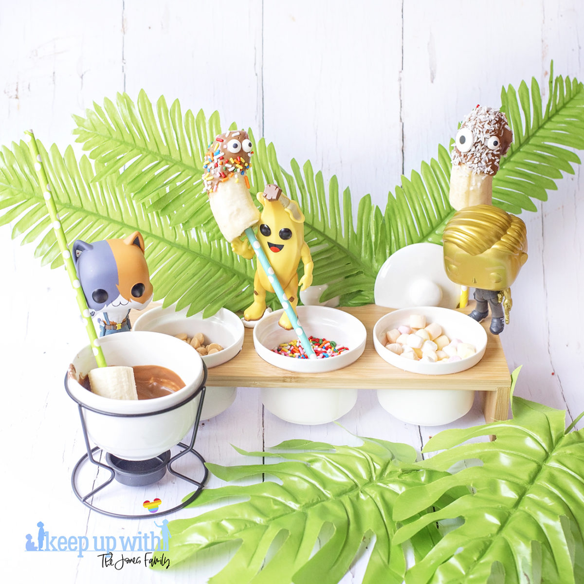 Image shows Peely's Banana Fortnite Fondue Bar, fun food for families. A Funko Pop Vinyl Peely, Meowscles and Midas stand on a fondue bar next to bananas on spotted coloured straws, a chocolate fondue and various toppings including edible eyes, sprinkles, mini marshmallows and peanut butter drops. Image by Sara-Jayne from Keep Up With The Jones Family.