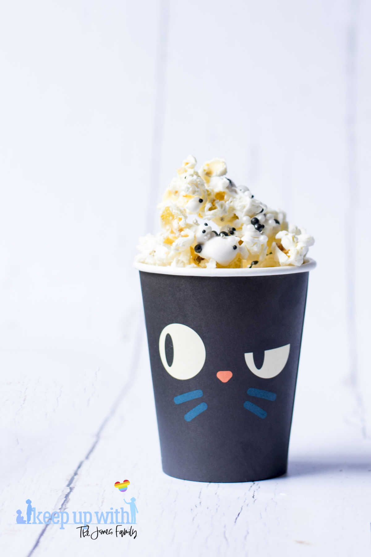 Image shows a black paper cup featuring yellow cat eyes and blue whiskers on the front, filled with Hocus Pocus Popcorn. Image by Keep Up With The Jones Family.