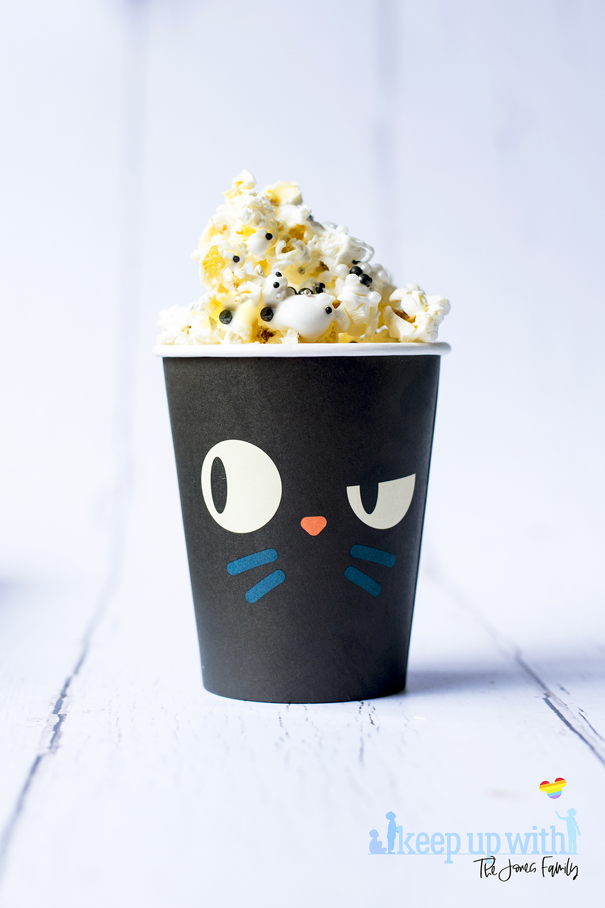 Image shows a black cat paper cup filled with disney's hocus pocus popcorn. image by keep up with the jones family.
