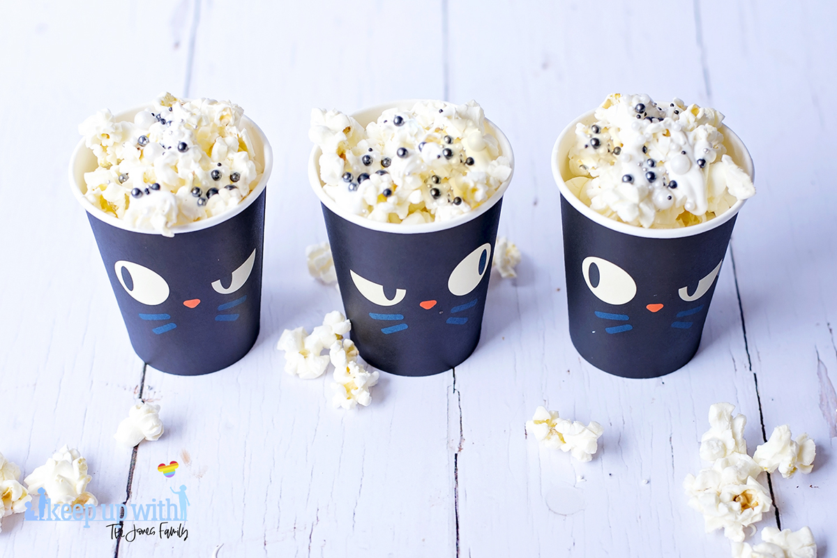 Image shows three cups of Disney's Hocus Pocus Popcorn in an overhead view on a white wooden tabletop. Image by keep up with thej jones family