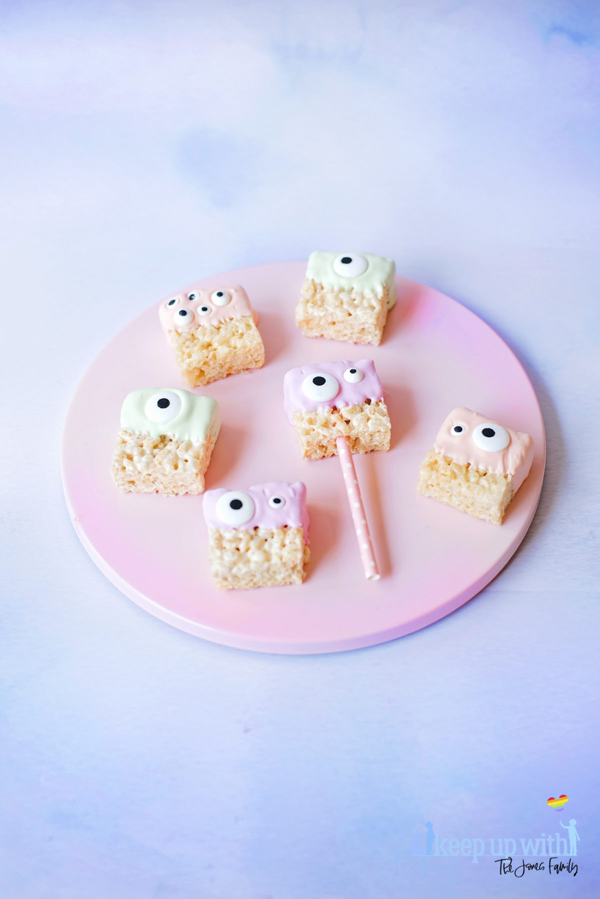 Image shows a pink cake plate with a variety of candy dipped pastel coloured alien rice krispie monsters. Image by Sara-Jayne for Keep Up With The Jones Family.