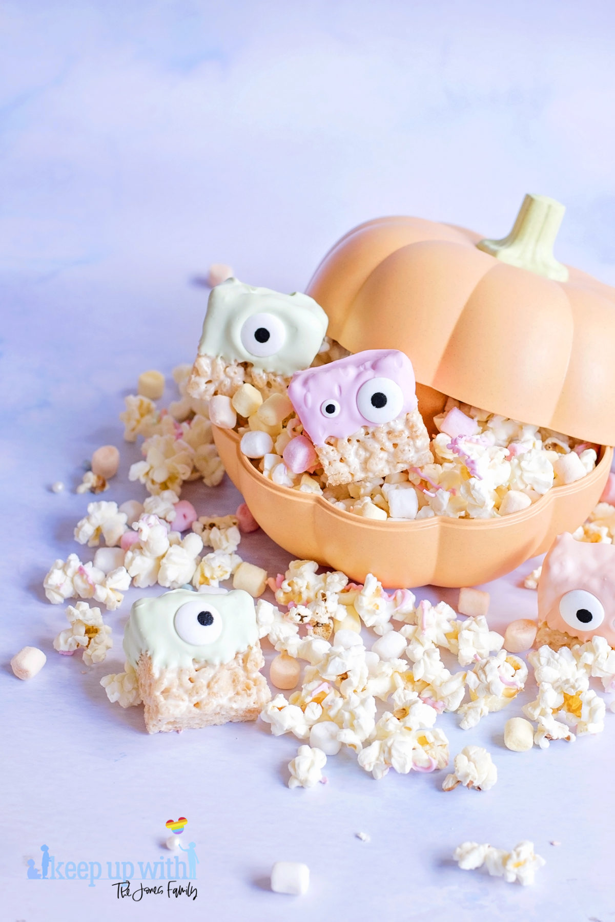 Image shows pastel coloured fun food rice krispie aliens or rice krispie monsters sat in a big orange pumpkin container filled with popcorn, which is spilling out.  Image by Sara-Jayne from Keep Up With The Jones Family.