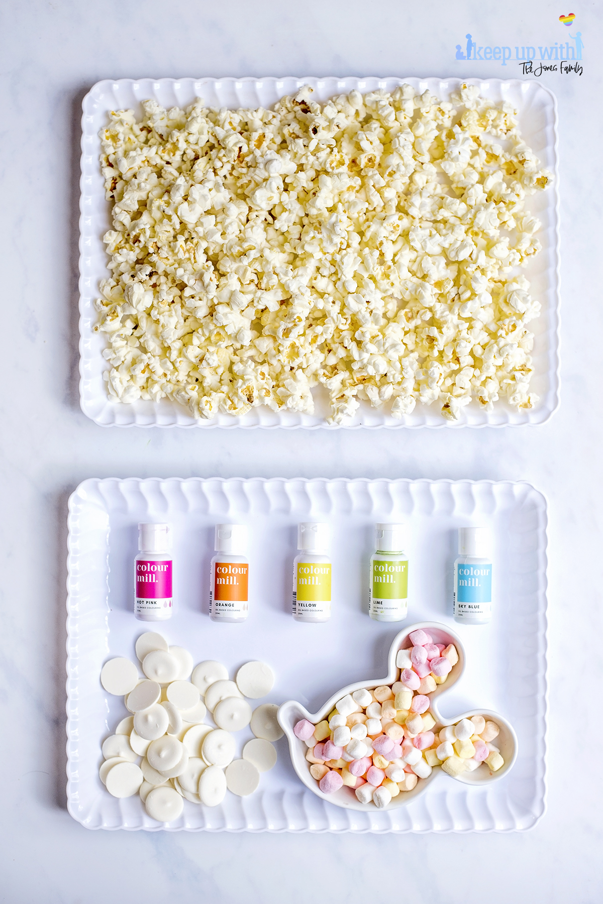 Image shows the ingredients used to make Mermaid Popcorn. Popcorn, spread evenly into a white scalloped tray, a pile of bright white candy melts, a mickey mouse shaped bowl of mini marshmallows and oil based food colourings from Colour Mill. Image by Sara-Jayne from keep Up With the Jones family.