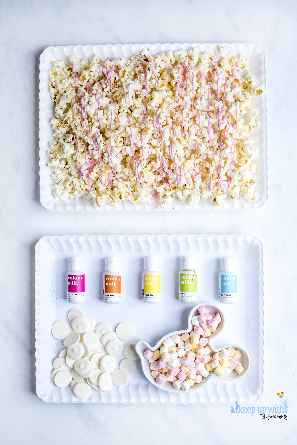 Image shows the ingredients used to make Mermaid Popcorn. Popcorn, spread evenly into a white scalloped tray, which has been coated in drizzled pink candy melts, a pile of bright white candy melts, a mickey mouse shaped bowl of mini marshmallows and oil based food colourings from Colour Mill. Image by Sara-Jayne from keep Up With the Jones family.