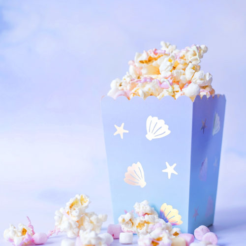 Image shows a carton of Mermaid Popcorn on a pale blue background. The popcorn is coated in pastel pink, orange and green candy melts, and there are mini pastel marshmallows and pearl sprinkles mixed in. The popcorn box is mermaid themed from Meri Meri. Image by Sara-Jayne from Keep Up With The Jones Family.