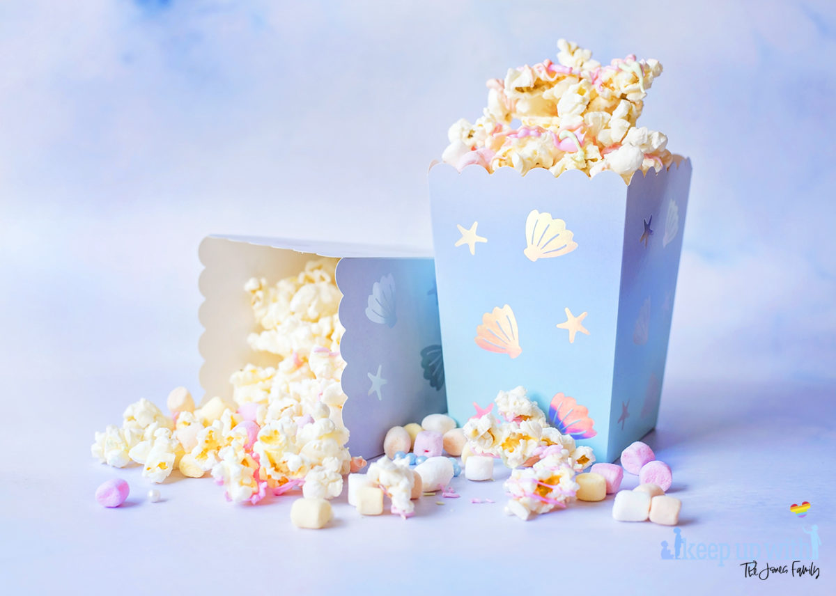 Image shows two cartons of Mermaid Popcorn on a pale blue background.  One is tipped over and popcorn is spilling out.  The popcorn is coated in pastel pink, orange and green candy melts, and there are mini pastel marshmallows and pearl sprinkles mixed in.  The popcorn box is mermaid themed from Meri Meri. Image by Sara-Jayne from Keep Up With The Jones Family.