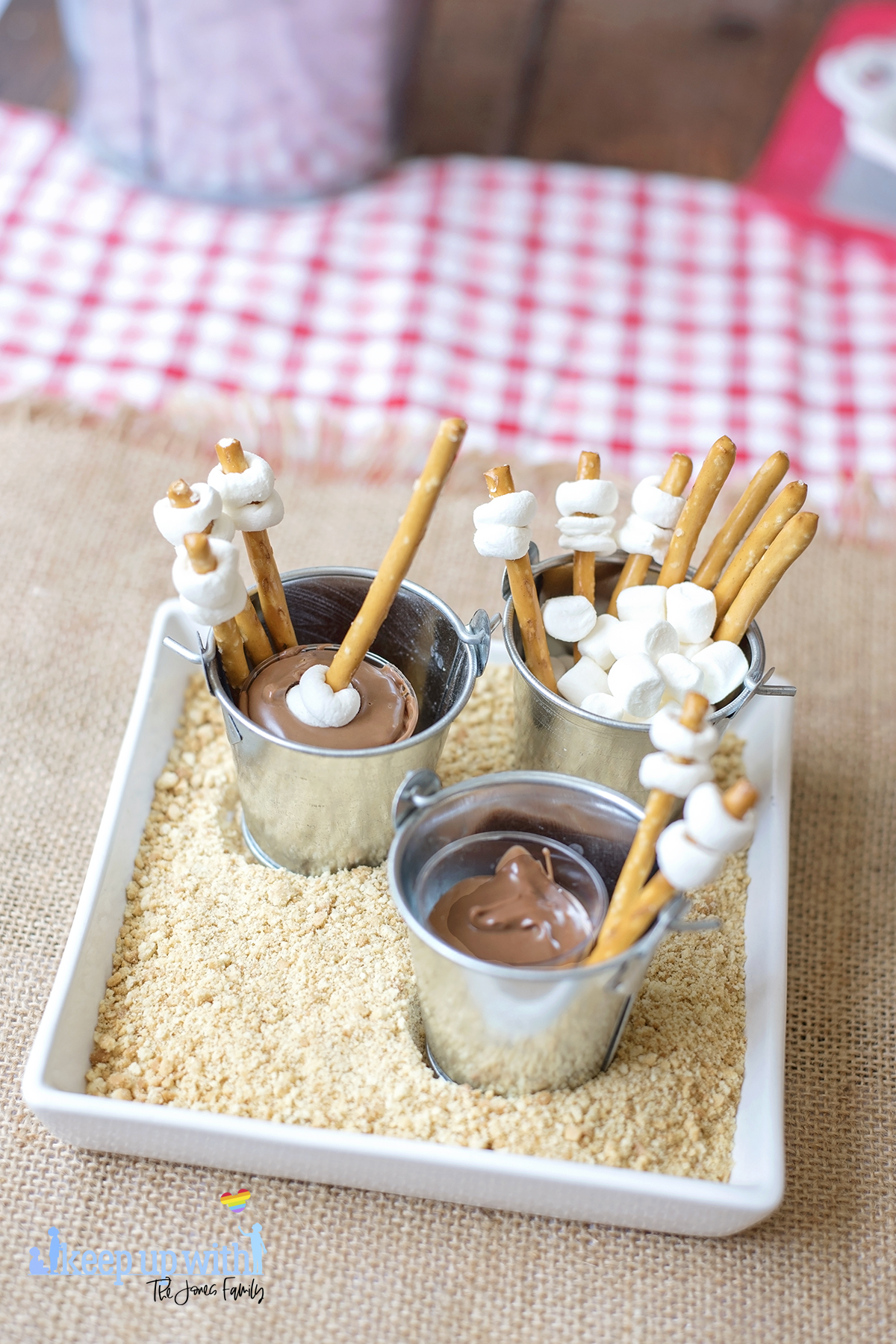 Image shows Mini Campfire Chocolate Fondue Buckets. Miniature galvanised steel buckets containing pretzel sticks with small marshmallows place on the ends like roasting marshmallow sticks, and a small plastic shot glass filled with melted chocolate. The buckets are placed on a white square plate filled with crushed digestive biscuit crumbs to look like sand. Image by Keep Up With The Jones Family.