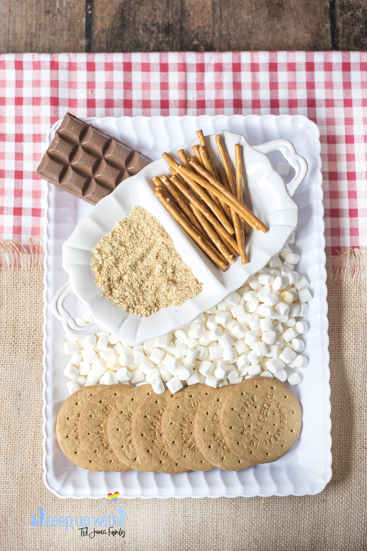 Image shows a white scalloped tray containing all of the ingredients to make Mini Campfire Chocolate Fondue Buckets. Mini marshmallows, digestive biscuits, pretzel sticks and chocolate. Image by Keep Up With The Jones Family.