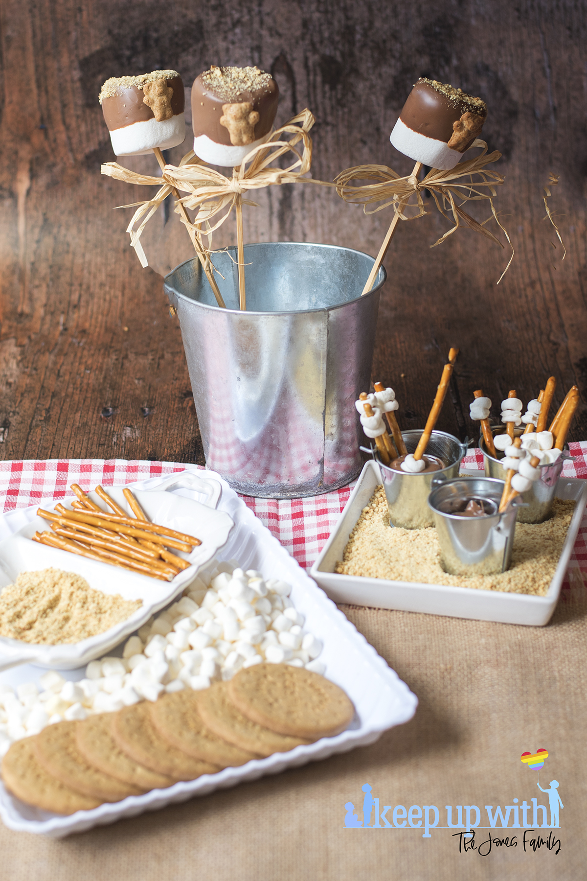 Image shows a dessert table set with Teddy Bear S'More Pops and Mini Campfire Chocolate Fondue Buckets. Image by Keep Up With The Jones Family.
